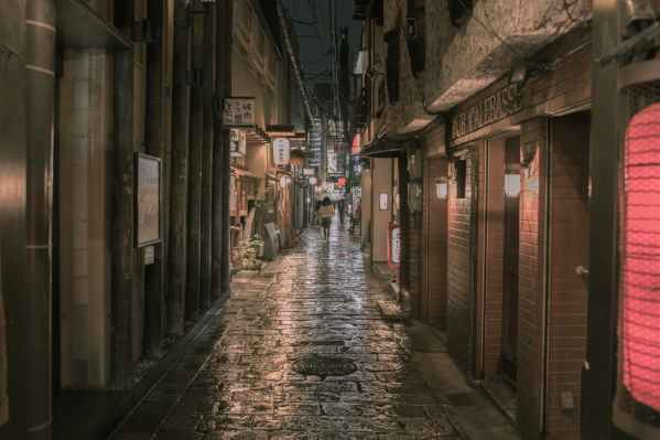 person walking on concrete alleyway at night t