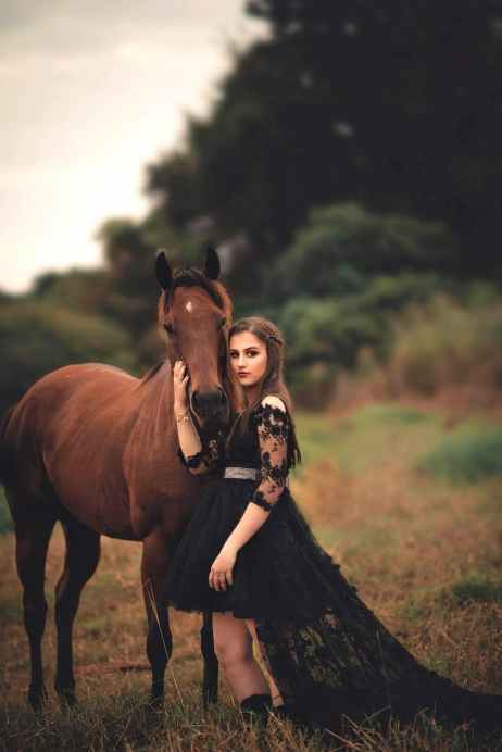 photo of woman wearing black dress beside horse