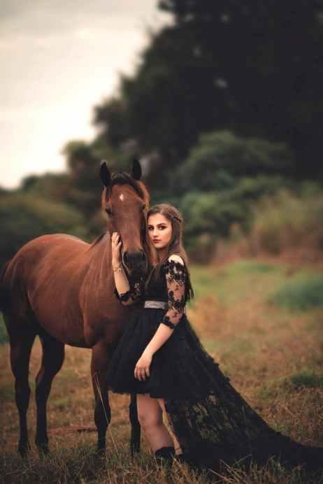 photo of woman wearing black dress beside horse
